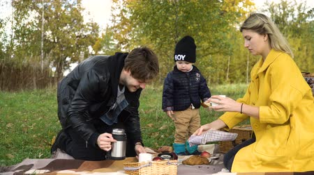 autumns : A young family with son at a picnic in the park on a sunny day.Family having picnic outdoors.Cute family picnicking in the park.Father pours tea on a picnic.Young smiling family doing a picnic on an autumns day.Family picnicking together.4K video,4K.