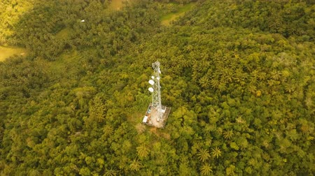 transmitter tower : Communication tower, cellphone tower in the jungle in the mountains. Aerial view: satellite, cellphone tower, on a mountain. View of a tropical island with palm trees and other vegetation, a mountain and white telecom radio tower. 4K video. Aerial footage Stock Footage