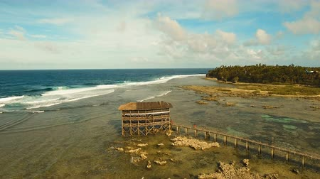 surfer paradise : Viewpoint in the ocean at Cloud Nine surf point, Siargao island , Philippines. Aerial view raised wooden walkway for surfers to cross the reef of siargao island to cloud 9 surf break mindanao. Siargao islands famous surf break cloud 9. Flying over the blu Stock Footage