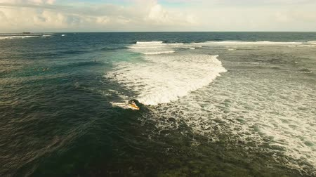 surfer paradise : Surfers at siargao islands famous surf break cloud 9 near mindanao the Philippines. Aerial view :People learning to surf at Cloud nine surfpoint in Siargao, Philippines. Stock Footage