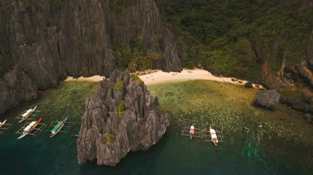tyrkysový : Beautiful beach with boats and tourists. Tropical bay in El Nido. Aerial view: bay and the tropical island. Aerial video. Tropical lagoon with turquoise water and white sand. Seascape: mountains, ocean. Philippines, El Nido. 4K video. Travel concept. Aeri