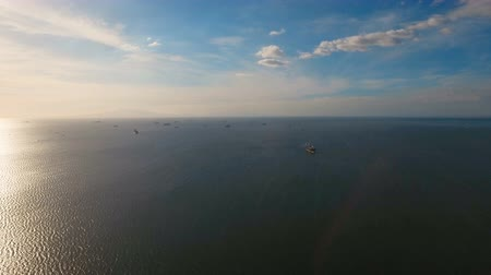 freighter : Aerial view Cargo ships in the Bay of Manila. Large container ship in the sea. Flying over the water surface of the sea with ships, blue sky and clouds. 4K video. Aerial footage. Philippines, Manila.
