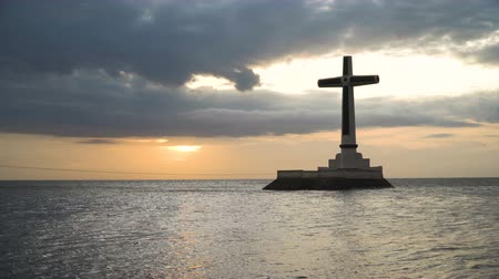 dark island : Sunken Cemetery cross in Camiguin Island, Philippines. Large crucafix marking the underwater sunken cemetary of the coast of camiguin island near mindanao in the Philippines. Catholic cross in the water on the background of sky and clouds.. The Sunken Cem