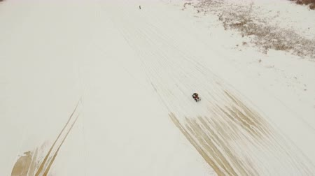 крайняя местности : Winter off-road racing side-by-side vehicles. Aerial view: Rally on the buggy on the snow on a winter day. Racing in the SXS class. Buggy, sports car on rally. Off Road Series racing. 4K video, drone footage.