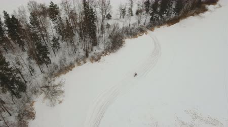 racers : Motorcycle rider on snowy motocross track. Aerial view: Mx rider on snow. Motocross rider on bike, motocross winter season race. Racer motorcycle rides on motocross snowy track in winter. 4K video, drone footage. Stock Footage