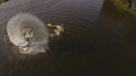 jet ski : Man on the flying board on the river, water jet spray.Man on the flying board flies over the lake water.Aerial:Fly board rider.Aerial video.4K video.