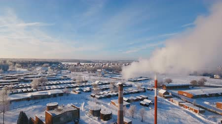 brick factory : Boiler room in the winter season, from the chimneys rise up clouds of steam. Pipes of a thermal power plant. Boiler house, pipe plant, boiler plant. Aerial footage, 4K video.