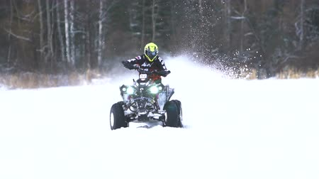 quadbike : ATV race on the snow. Rider driving in the quadbike race. Man riding ATV in sand in protective clothing and a helmet. Racer rides a quad motorbike in the cross racing. Quadrocycle on the snow cover. Slow motion.