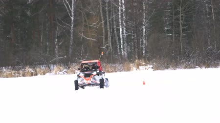 racers : Winter off-road racing side-by-side vehicles. Rally on the buggy on the snow on a winter day. Racing in the SXS class. Buggy, sports car on rally. Off Road Series racing. Slow motion. Stock Footage