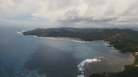 idylický : The coast of the tropical island with the mountains and the rainforest on a background of ocean with big waves.Aerial view: sea and the tropical island with rocks, beach and waves. Seascape: sky, clouds, rocks, ocean. 4K video. Philippines, Catanduanes. 4
