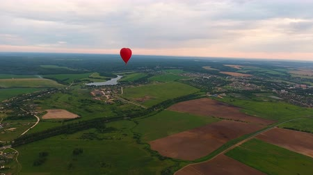 tej : Red balloon in the shape of a heart.Aerial view:Hot air balloon in the sky over a field in the countryside, beautiful sky and sunset. Aerostat fly in the countryside. 4K video,ultra HD.