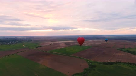 tej : Red balloon in the shape of a heart.Aerial view:Hot air balloon in the sky over a field in the countryside.Aerostat fly in the countryside. 4K video,ultra HD.