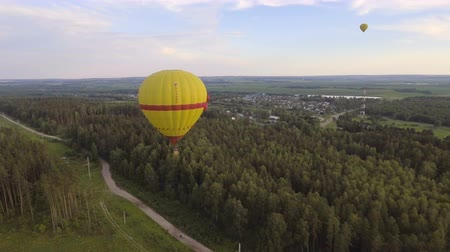 tej : Aerial view:Hot air balloon in the sky over a field in the countryside in the beautiful sky and sunset.Aerostat fly on the countryside. 4K video,ultra HD.