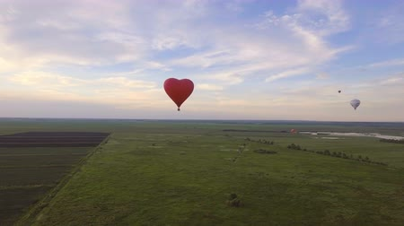 dirigível : Aerial view:Hot air balloon in the sky over a field in the countryside in the beautiful sky and sunset.Aerostat fly on the countryside. 4K video,ultra HD.