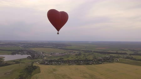 tej : Red balloon in the shape of a wheat heart.Aerial view:Hot air balloon in the sky over a field in the countryside, beautiful sky and sunset.Aerostat fly in the countryside. 4K video,ultra HD.