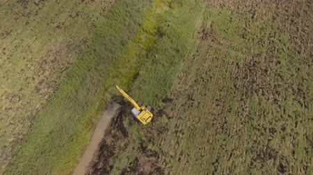 ditch : Excavator is digging an irrigation canal.Aerial view:Excavator digging a deep trench.excavator is digging an drainage canal in the agricultural field.4K,UHD.