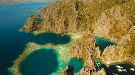 flying video : Aerial view: Twin Lagoon with blue, azure water in the middle of small islands and rocks. Beach, tropical island, sea bay and lagoon, mountains with forest, Palawan, Coron. Busuanga. Seascape, tropical landscape. Aerial video. Philippines. 4K video Travel