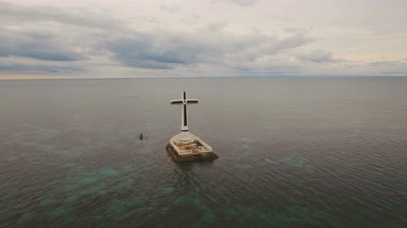 могильная плита : Aerial view Sunken Cemetery cross in Camiguin Island, Philippines. Large crucafix marking the underwater sunken cemetary of the coast of camiguin island near mindanao in the Philippines. Catholic cross in the water on the background of sky and clouds.. Th Стоковые видеозаписи