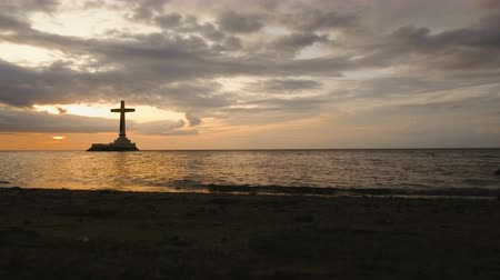 надгробная плита : Aerial view Sunken Cemetery cross in Camiguin Island, Philippines,sunset. Large crucafix marking the underwater sunken cemetary of the coast of camiguin island near mindanao in the Philippines. Catholic cross in the water on the background of sky and clou Стоковые видеозаписи