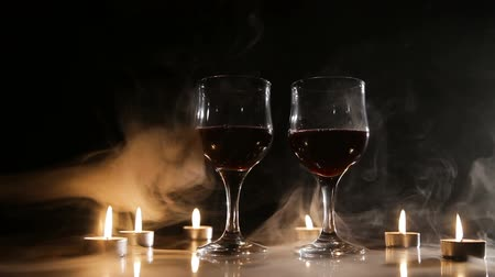 каберне : Two glasses of wine on black background and burning candles in the smoke..Glasses of red wine over candlelight and darkness.Romantic atmosphere with wine glasses and candles.