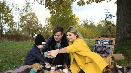 autumns : Smiling family taking selfie sitting on the grass in a city park.A young family with son at a picnic in the park on a sunny day.Family having picnic outdoors.Cute family picnicking in the park.Young smiling family doing a picnic on an autumns day.Family p Stock Footage