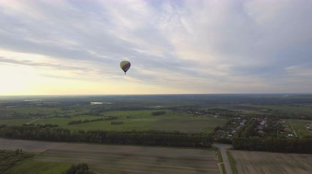 dirigível : Hot air balloons in the sky over a field in the countryside.Aerial view:Hot air balloons in the sky over a field in the countryside in the beautiful sky and sunset.Aerostat fly in the countryside. 4K video,ultra HD.