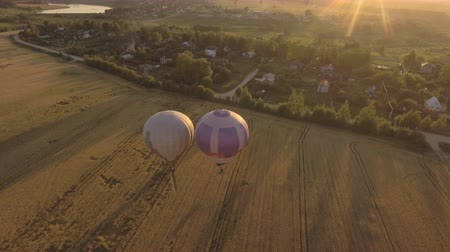 tej : Hot air balloons in the sky over wheat field in the countryside.Aerial view:Hot air balloons in the sky over a field countryside beautiful sky and sunset. 4K video,ultra HD.