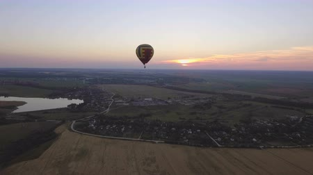 tej : Hot air balloon in the sky over wheat field in the countryside.Aerial view:Hot air balloon in the sky over a field countryside the beautiful sky and sunset.Aerostat fly the countryside. 4K video,ultra HD. Stock mozgókép