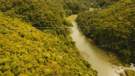 adrenalin : People have fun a zip line through a canyon with a river in the rainforest jungle. Aerial view, tourist attraction at the zipline attraction in the jungle on the island of Bohol. 4K video. Travel concept. Aerial footage. Dostupné videozáznamy
