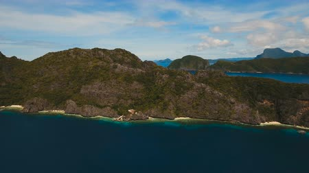 türkiz : Tropical islands, aerial view. Aerial view: sea and the tropical island. Tropical bay in El Nido. Archipelago El Nido.Sandy beaches of the wild islands. Philippines National Marine Park. Aerial video. Seascape: sky,clouds and mountains rocks,ocean. 4K vid Stock mozgókép
