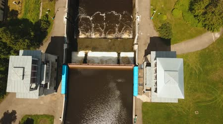 sluice : Sluice Gates on the River. Aerial view river sluice construction, water river gateway. Shipping channel on the river. 4K, flying video, aerial footage