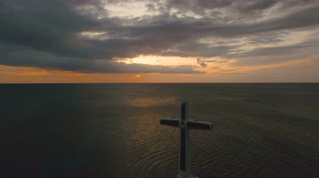 işaretler : Aerial view Sunken Cemetery cross in Camiguin Island, Philippines,sunset. Large crucafix marking the underwater sunken cemetary of the coast of camiguin island near mindanao in the Philippines. Catholic cross in the water on the background of sky and clou Stok Video