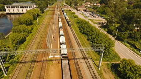 способ : Freight train with cisterns and containers on the railway. Aerial view Container Freight Train, Locomotive to the railway station. 4K, flying video, aerial footage.