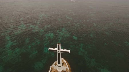dark island : Aerial view Sunken Cemetery cross in Camiguin Island, Philippines. Large crucafix marking the underwater sunken cemetary of the coast of camiguin island near mindanao in the Philippines. Catholic cross in the water on the background of sky and clouds.. Th Stock Footage
