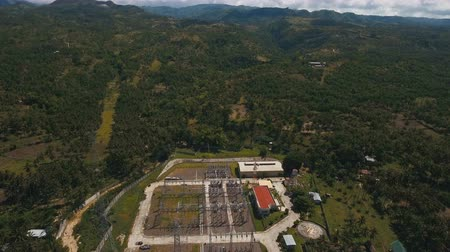 watt : Aerial view high voltage power transformer substation in tropical forest. Power station in the mountains. Electrical power transformer in high voltage substation. 4K video. Aerial footage.