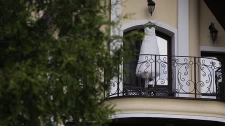 veranda : Wedding dress on the balcony of the luxury villa. wedding dress of the bride hangs on the veranda of the house. Dostupné videozáznamy