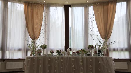 banquete : Festive, decorated banquet hall for weddings. Beautiful elegant wedding reception table arrangement. Tables setting at a luxury wedding hall. Stock Footage