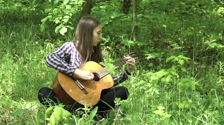 gitáros : Young girl in forest with guitar in the garden. Teenage girl playing the guitar in nature. Girl play solo guitar in green nature park. 4K video Stock mozgókép
