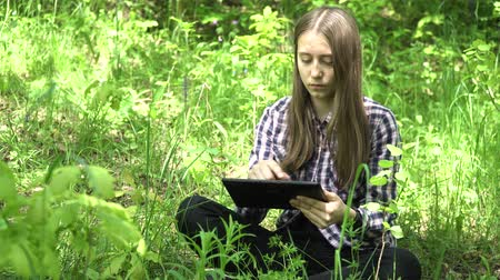 bonitinho : Teenage girl using tablet in green park. Cute young girl with digital tablet in a summer forest. 4K video