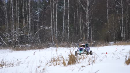 atv : Winter racing side-by-side vehicles. Rally on the buggy on the snow on a winter day. Racing in the SXS class. Buggy, sports car on rally. Off Road Series racing. Slow motion.