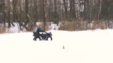 yarışçı : ATV race on the snow. Rider driving in the quadbike race. Man riding ATV in sand in protective clothing and a helmet. Racer rides a quad motorbike in the cross racing. Quadrocycle on the snow cover. Slow motion.