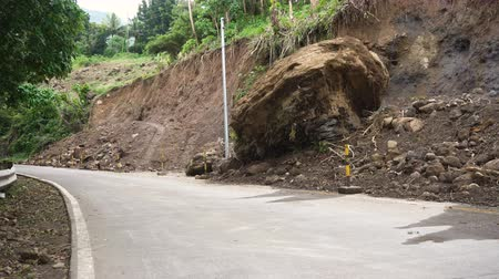 yıkıldı : Landslides and rockfalls on the road in the mountains. Mud and rocks blocking the road.Destroyed rural road landslide damaged in powerful flood. Collapsed on the mountain. Philippines, Camiguin. 4K video.