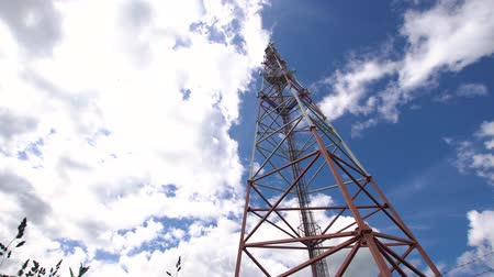 emisor : Cell phone tower against a blue sky. Tower of communications with a lot of different antennas under blue sky and clouds. Telecommunication tower with blue sky. 4K video