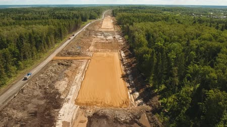 vyhloubení : Construction of a new road in the forest area. Aerial view construction road place. Construction machinery for the construction of a road in the forest. 4K, flying video, aerial footage