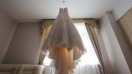 casar : White wedding dress of the bride in the interior of modern rooms in hotels. luxury wedding dress with a long train and skirt with ruffles on a hanger in the room of the bride.