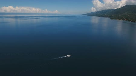 cebu : Aerial view of motor boat in sea. Aerial image of motorboat floating in a turquoise blue sea water. Sea landscape with wake of small fast motorboat. Tropical landscape. Philippines, Cebu. 4K video. Travel concept. Aerial footage.
