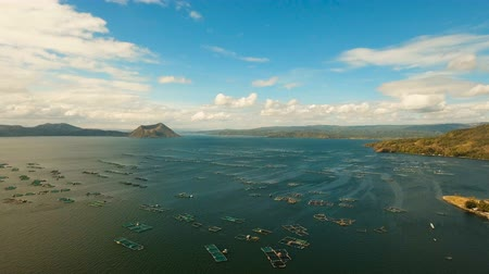 flying video : Fish Farm with floating cages in lake Taal. Aerial view: Fish farming with cages for whitebait on the surface of the water. Luzon, Philippines.