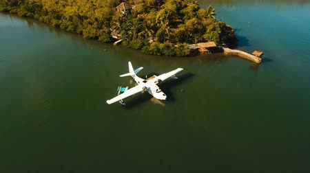 hydroplane : Aerial view: White Seaplane parked in the sea bay of the tropical island. Hydroplane in the lagoon and coastline. Philippines,Palawan, Busuanga. 4K video. Travel concept, Aerial footage. Stock Footage