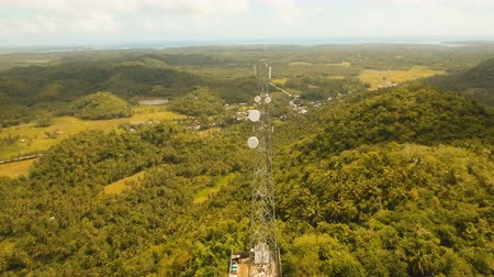 anten : Communication tower, cellphone tower in the jungle in the mountains. Aerial view: satellite, cellphone tower, on a mountain. View of a tropical island with palm trees and other vegetation, a mountain and white telecom radio tower. 4K video. Aerial footage Stok Video