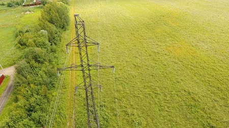 pilon : Power pylons and high voltage lines in an agricultural landscape. Aerial view row of high-voltage masts in the field. Electricity transmission power lines. Aerial footage.